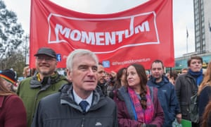John McDonnell in front of a Momentum banner