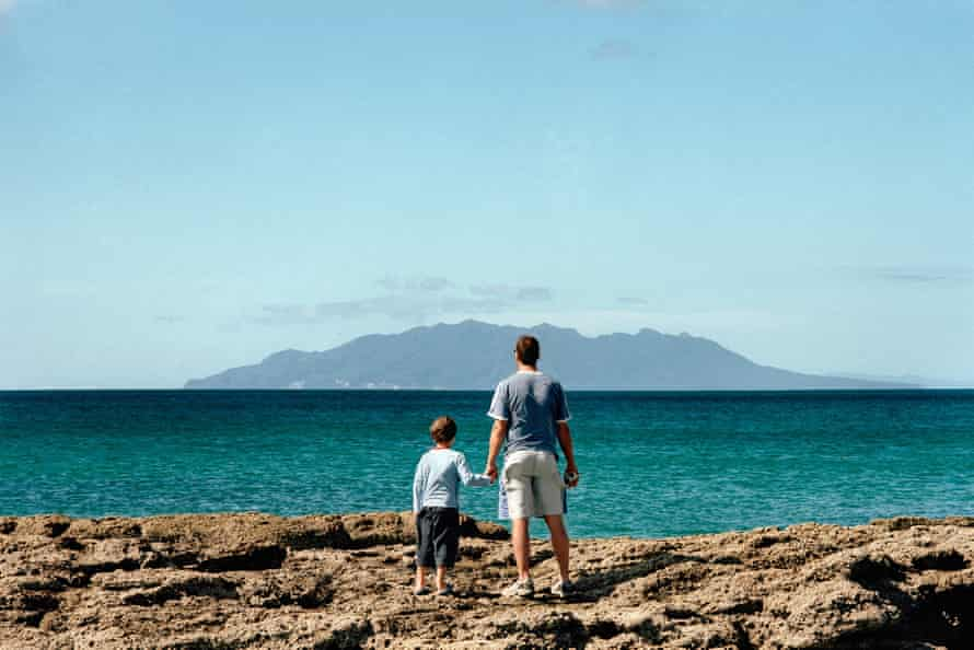 Boy and man stare out to sea.