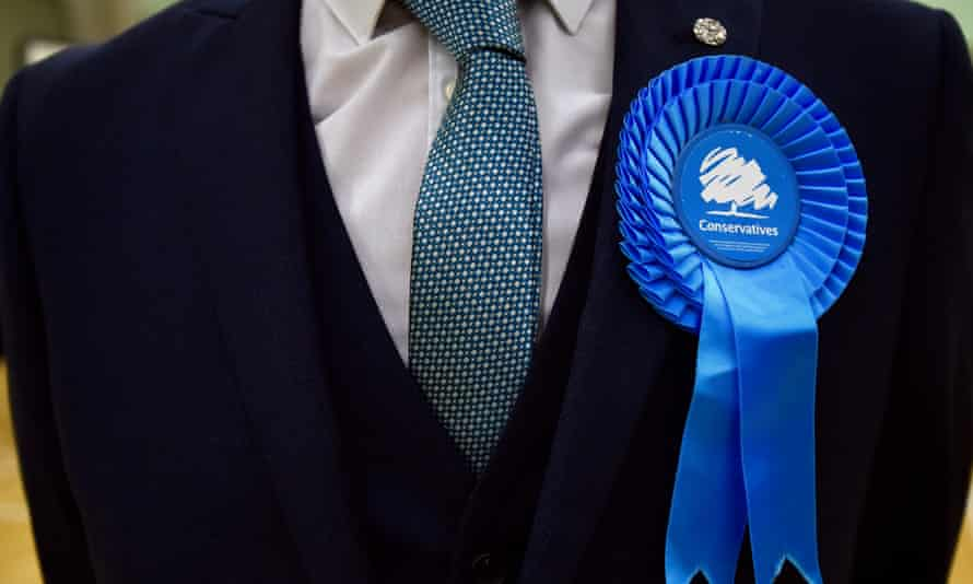 Man in suit wearing Conservative party rosette
