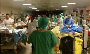 This is the scene from inside a packed Paris hospital as surgeons struggle to save the lives of countless victims of Friday's terror attacks. The dramatic photograph, taken at St Louis Hospital, shows doctors working in crammed conditions after 132 people were killed.