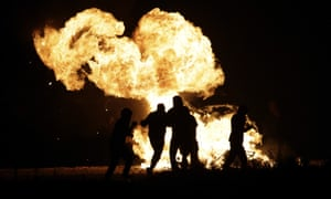 Camp residents run past a fire on Sunday night.