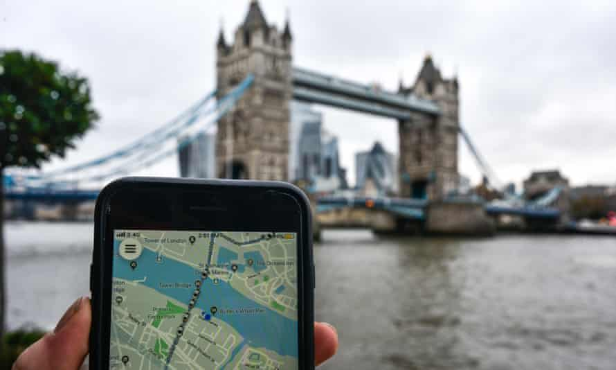 Phone showing Uber app with Tower Bridge in the background