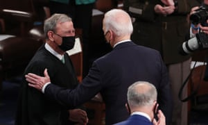 John Roberts (L) is greeted by Joe Biden as the president arrived to deliver his first address to a joint session of Congress in the House chamber of the US Capitol in Washington, DC, in April.