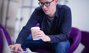 Student holding coffee cup and using computer.