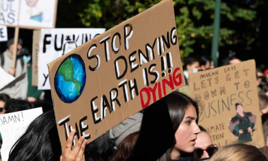 A protester holds a 'stop denying, the Earth is dying' placard at a climate change rally in Melbourne