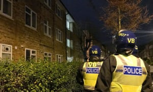Police officers prepare to raid a property as part of an operation to tackle county drugs lines.
