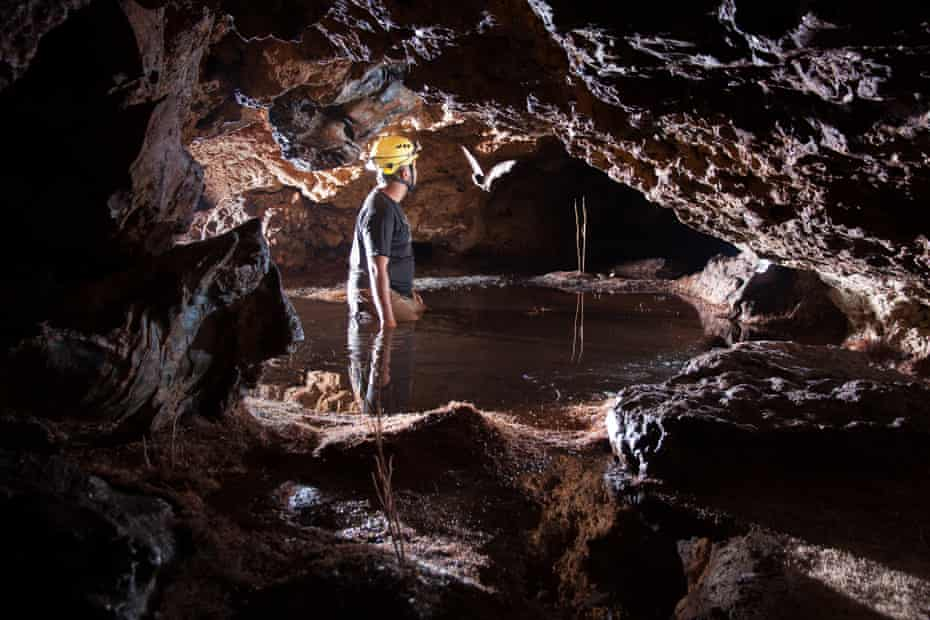 a scientist explores a partially flooded ironstone cave in Vale do Rio Peixe Bravo River, northern Minas Gerais State, Brazil