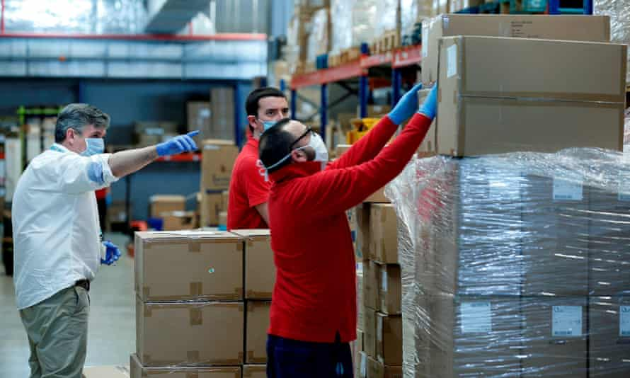 Workers sort out protective equipment from China at a warehouse in Valencia, Spain.