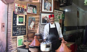 Cook, wearing a red fez hat, tends tagines at the street-food stall Terrasse Bakchich in Marrakech, Morocco.
