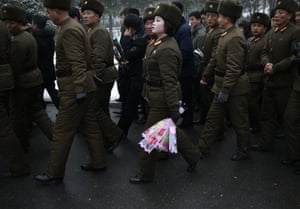 Pyongyang, North Korea: A member of the military holds flowers to be laid in memory of the leaders Kim Il-sung and Kim Jong-il at the Mansu Hill Grand Monument