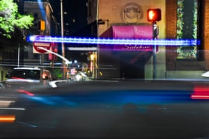 """A Baltimore City Police car whizzes by the exterior of The Sidebar, more famously known as police bar """"Kavanaugh's"""", photograph by JM Giordano"""