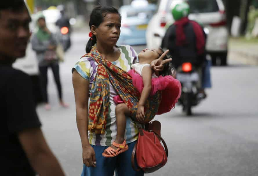 A woman carries her baby as she signals to show that she's for hire as a 'jockey'.