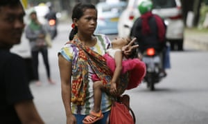A woman carries her baby as she signals to show that she's for hire as a 'jockey' to help drivers cheat a peak time traffic rule of three people to one car during rush hour in Jakarta, Indonesia.