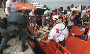 Members of the Spanish Red Cross and Civil Guard help a man off a boat