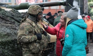 Polish people speak to a member of the US army.