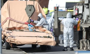 Soldiers wearing protective clothing prepare to take away the recovery vehicle in Gillingham, Dorset