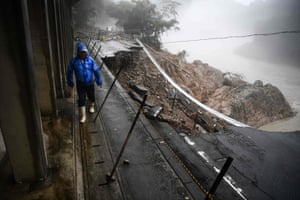 A man walks by a collapsed road in Kuma, in Kumamoto prefecture
