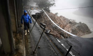 A man walks by a collapsed road caused by heavy rain in Kuma, Kumamoto prefecture. Flooding and heavy rains have killed 58 people.