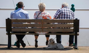 Penarth, Wales. A dog enjoys the shade of a bench on the esplanade.