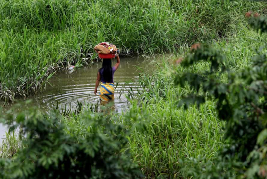 A woman carries her laundry in the Atrato river, Colombia, which has been recognised as a legal entity.