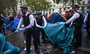 Police officers remove tents belonging to Extinction Rebellion activists in Westminster.