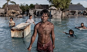 A family wades through sea water that flooded their village in Kiribati central Pacific. Warmer oceans are a major factor in increasing the severity of storms and extreme rainfall.