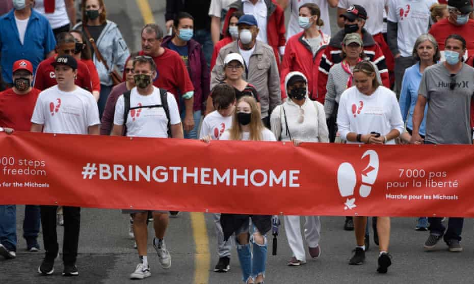people march behind banner that says 'bring them home'