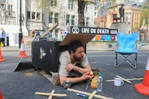 A protester lying inside a makeshift coffin at Parliament Square