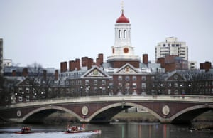 Rowers paddle along the Charles River past the Harvard College campus in Cambridge, Massachusetts.