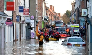 A rescuer throws a Wellington boot to a trapped resident in Walmgate, York, after the rivers Foss and Ouse burst their banks.