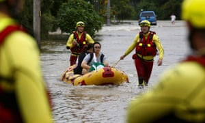 Queensland Fire and Emergency Services crew members use an inflatable boat to pull residents through floodwaters at Hermit Park in Townsville