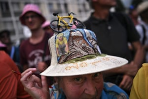 A fan sporting a fancy hat with a portrait of Julian Alaphilippe, wearing the overall leader's yellow jersey and a yellow miniature bike, poses before the nineteenth stage between Saint-Jean-de-Maurienne and Tignes.