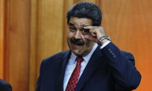 Nicolás Maduro gestures to military leaders to keep their eyes open at the end of a press conference inside the presidential palace in Caracas, Venezuela, on 25 January.