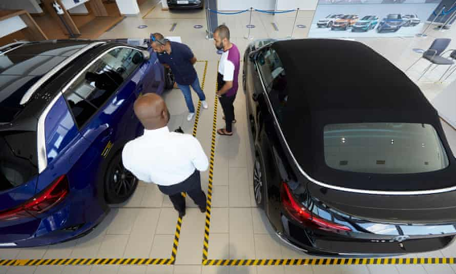 Sajul Islam and a friend look at cars at a Volkswagen dealership in Loughton, Essex.