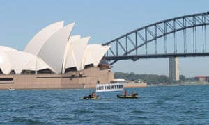 Protesters representing GetUp, ActionAid, Amnesty International and Greenpeace hold a #LetThemStay banner between two boats on Sydney harbour on Sunday morning.