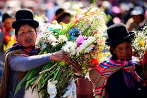 Women carry flowers during the procession in La Paz.