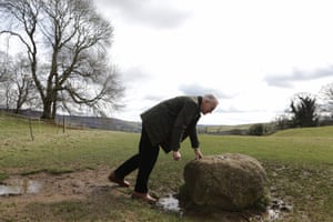 A man touches the boundary stone in Eyam from which no resident could pass during the village's isolation in 1666.