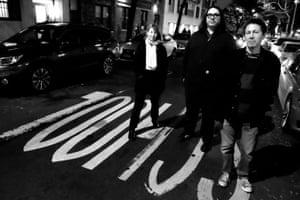 Yo La Tengo standing on a narrow city street at night time
