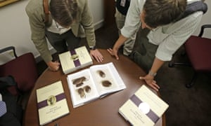 People look at pictures of the smooth, brown, egg-sized rock shown in the printer's manuscript of the Book of Mormon following a news conference in Salt Lake City.