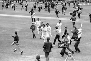 Bob Willis leading the side off after England's sensational victory over Australia in the third Ashes Test at Headingley in 1981 as fans run on to celebrate.