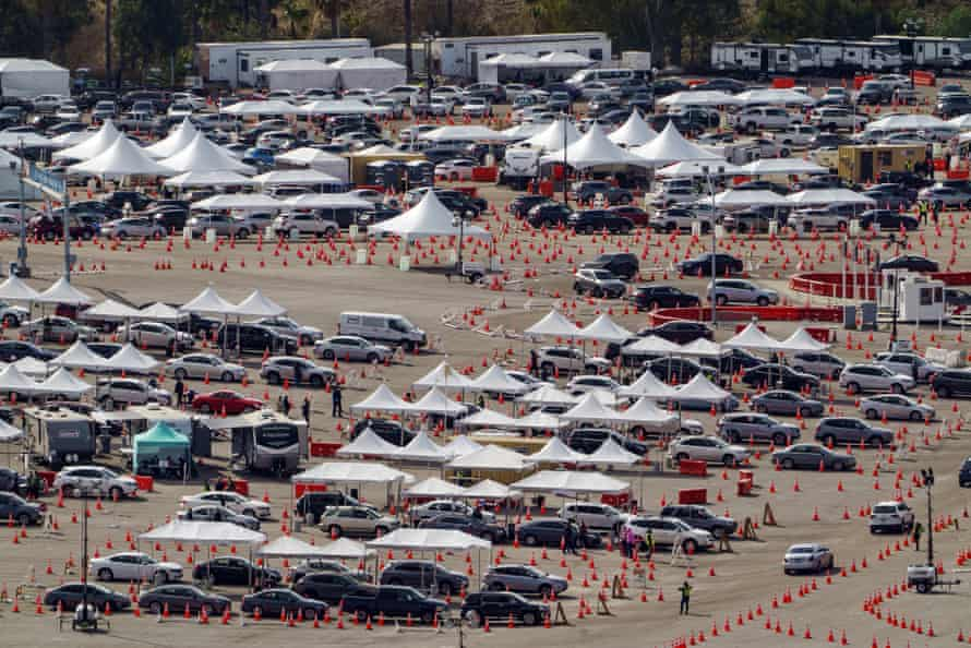 Drivers queue at a mass COVID-19 vaccination site at the Dodger Stadium parking lot.