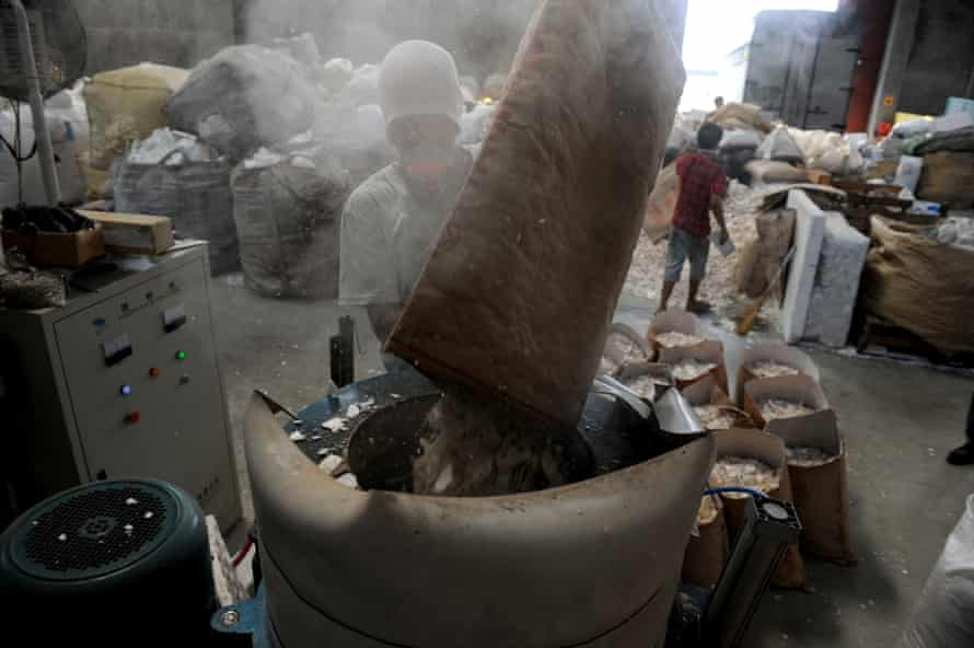 A worker puts styrofoam in a shredder at a recycling plant in Valenzuela City, north of Manila.