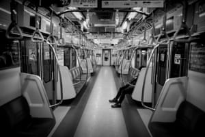 A commuter sits in a deserted subway car