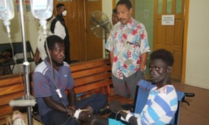 Dominic Stally (left) and another survivor talk to John C Balavu (centre), the Papua New Guinean high commissioner to the Solomon Islands at the National Referral Hospital in Honiara after their rescue.