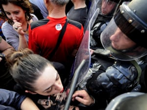 Jasmina Golubovska does her lipstick in the shield of a policeman in front of a government building in Skopje, Macedonia, on  5 May, 2015