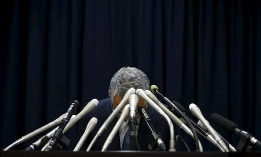 Akira Amari bows at a news conference where he said he was resigning to take responsibility for a political funding scandal.