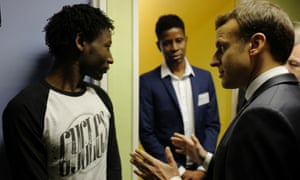 French President Emmanuel Macron talking to Ahmed Adam, left, from Sudan during his visit to a migrant center in Croisilles, northern France, earlier today.