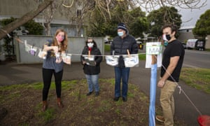 Janet (left) and Steve (right) provide locals Lilian and Chris with some homemade masks in South Melbourne on Monday.