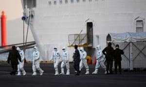 People in protective suits walk from the Diamond Princess cruise ship in Japan.