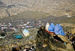 Kabul, 2006. An Afghan family sits on the mountain side as thousands of people gathered to look down on the Sakhi shrine, where a ceremony celebrating the New Year took place.